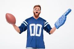 Homme enthousiaste avec la boule de rugby et doigt de fan encourageant vers le haut de d'isolement Photographie stock libre de droits