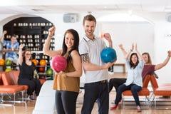 Homme enthousiaste et femme avec des boules de bowling dans le club Photographie stock