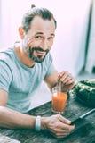 Homme enthousiaste joyeux buvant du jus frais dans la cuisine photos libres de droits