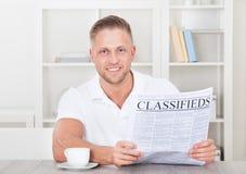 Homme enthousiaste lisant les classifieds Photos libres de droits