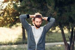 Homme enthousiaste touchant sa tête en parc Image stock
