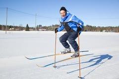 Homme entre deux âges branchant dans le ciel avec des skis Images stock