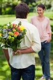 Homme environ pour étonner son ami avec un bouquet des fleurs Photo libre de droits