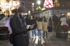 Homme envoyant le message pendant la nuit de ville Images stock