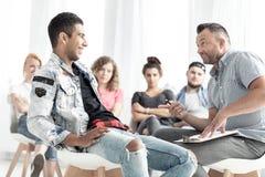Homme espagnol de sourire parlant à un conseiller pendant la thérapie pour le yo Photos libres de droits