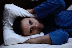 Homme essayant de dormir dans son lit Photographie stock libre de droits