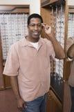 Homme essayant différents verres d'oeil aux optométristes image libre de droits