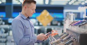 Homme essayant le nouveau téléphone intelligent Intérieur de magasin de technologie banque de vidéos