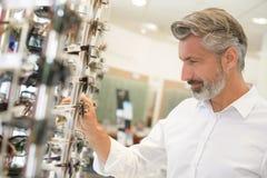 Homme essayant sur des lunettes au sourire d'optométristes photographie stock libre de droits