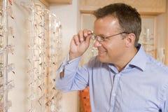 Homme essayant sur des lunettes aux optométristes photos stock