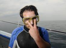 Homme essayant sur un masque de scaphandre Photographie stock libre de droits