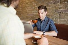Homme et ami dans le café utilisant l'ordinateur Images libres de droits