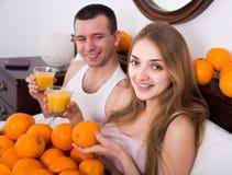 Homme et amie buvant du jus d'orange serré dans le lit Images libres de droits