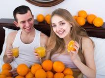 Homme et amie buvant du jus d'orange serré dans le lit Photo libre de droits