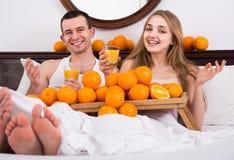 Homme et amie buvant du jus d'orange serré dans le lit Photographie stock libre de droits