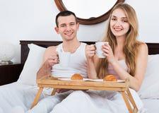 Homme et amie heureux avec le petit déjeuner savoureux Photos libres de droits