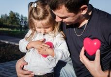 Homme et bébé tenant un coeur de plastique de deux rouges le père étreint la fille Photos libres de droits