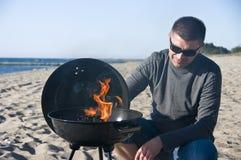 Homme et barbecue sur la plage Photographie stock