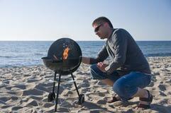Homme et barbecue sur la plage Photo stock