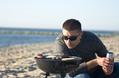 Homme et barbecue sur la plage Photo stock