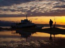 Homme et bateaux dans le coucher du soleil Photographie stock libre de droits