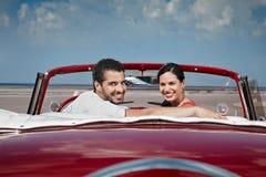 Homme et belle femme étreignant dans le véhicule de cabriolet Images libres de droits