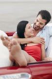 Homme et belle femme étreignant dans le véhicule de cabriolet Photo stock