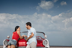 Homme et belle femme se penchant sur le véhicule de cabriolet Photos libres de droits