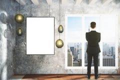 Homme et cadre de tableau et lampes vides sur le mur en béton Photo stock
