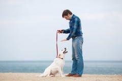 Homme et chien ayant l'amusement sur le bord de la mer Photos libres de droits