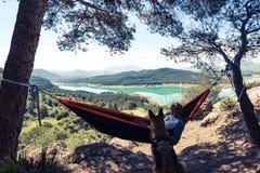 Homme et chien d'envie de voyager détendant à l'hamac en montagnes Image stock