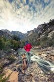 Homme et chien d'envie de voyager en montagnes sauvages par la rivière Photographie stock