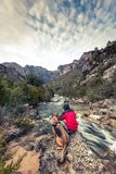 Homme et chien d'envie de voyager en montagnes sauvages par la rivière Images stock