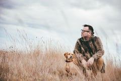 Homme et chien dans la haute herbe Photographie stock