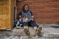 Homme et chien dormant tout en se reposant sur un béton contre le mur de briques images stock