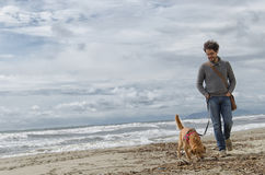 Homme et chien marchant sur la plage Photo stock