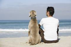 Homme et chien se reposant sur la plage Images libres de droits