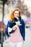 Homme et chien soumis jeune femme caucasienne rousse avec des taches de rousseur sur le chien hirsute noir et blanc de race de ch Photos libres de droits