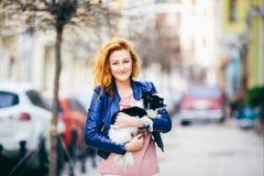 Homme et chien soumis jeune femme caucasienne rousse avec des taches de rousseur sur le chien hirsute noir et blanc de race de ch Photo stock