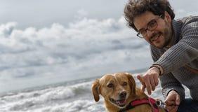 Homme et chien sur la plage Image stock