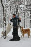 Homme et chiens dans la neige Images stock