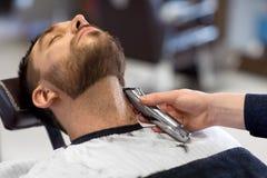 Homme et coiffeur avec la barbe de coupe de trimmer au salon photographie stock libre de droits