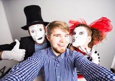 Homme et couples drôles des pantomimes prenant une photo de selfie Image libre de droits