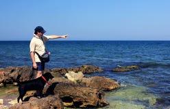 Homme et crabot au bord de la mer Photographie stock