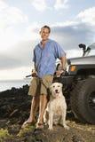 Homme et crabot par SUV à la plage Photos libres de droits