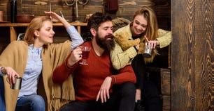 Homme et dames sur les visages heureux discutant et buvant du vin chaud Les amis ont l'amusement, parlant et buvant les boissons  Photos libres de droits