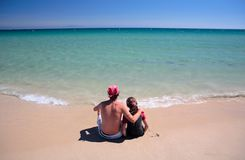 Homme et descendant s'asseyant sur la plage abandonnée ensoleillée Photos stock