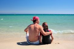 Homme et descendant s'asseyant sur la plage abandonnée ensoleillée Photographie stock libre de droits