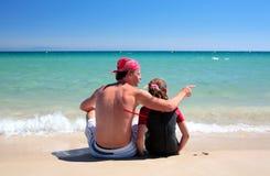 Homme et descendant s'asseyant sur la plage abandonnée ensoleillée Photographie stock