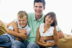 Homme et deux enfants en bas âge dans le sourire de salle de séjour Photo libre de droits
